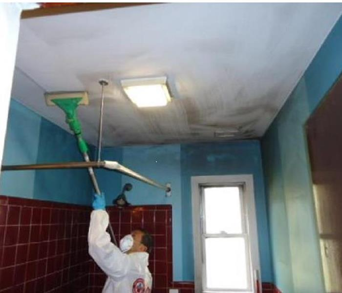 fire technician cleaning soot from ceiling of a bathroom