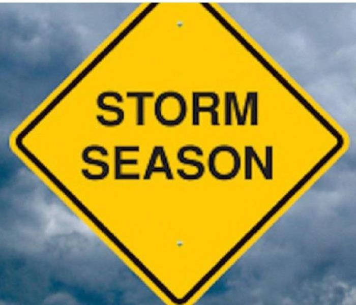 yellow diamond sharped sign with the words storm season